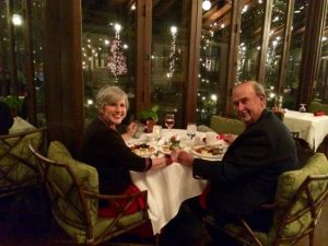 Senior couple holding hands at a table set for the holidays