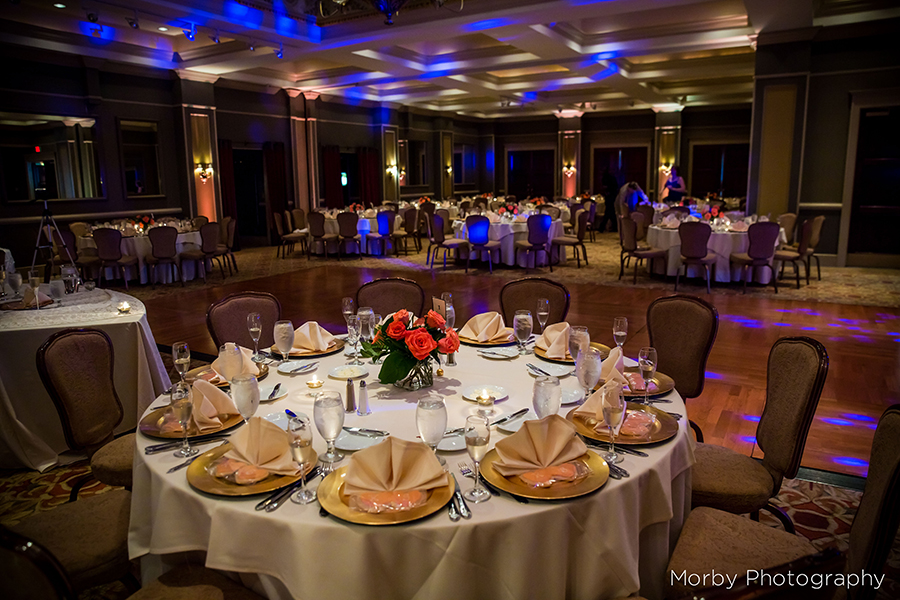 Formal table setting in an elegant ballroom lit with blue lights