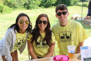 Three young people in Crab Fest t-shirts smiling at the camera